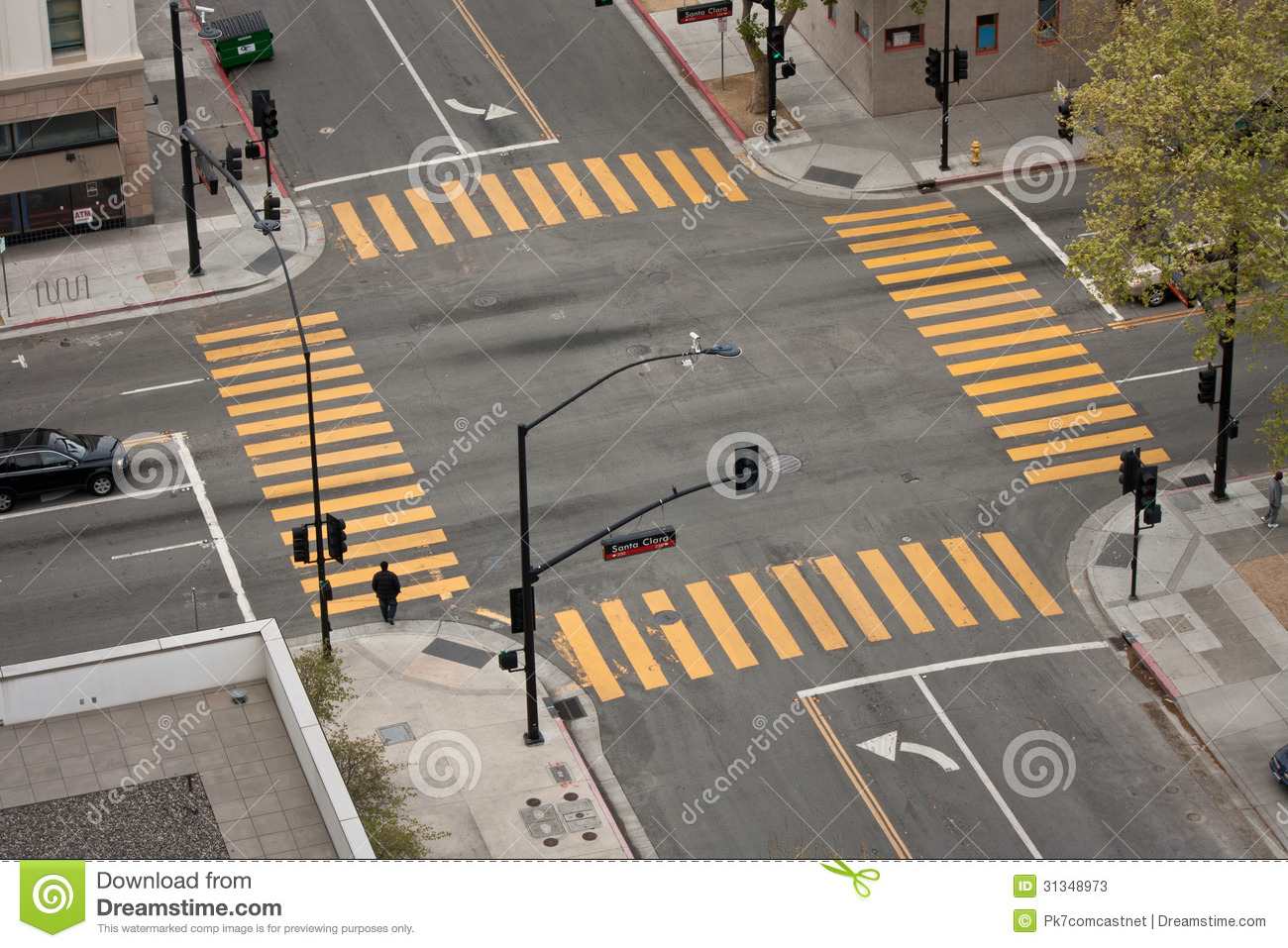 high angle view of an almost empty street intersection, with yellow ...