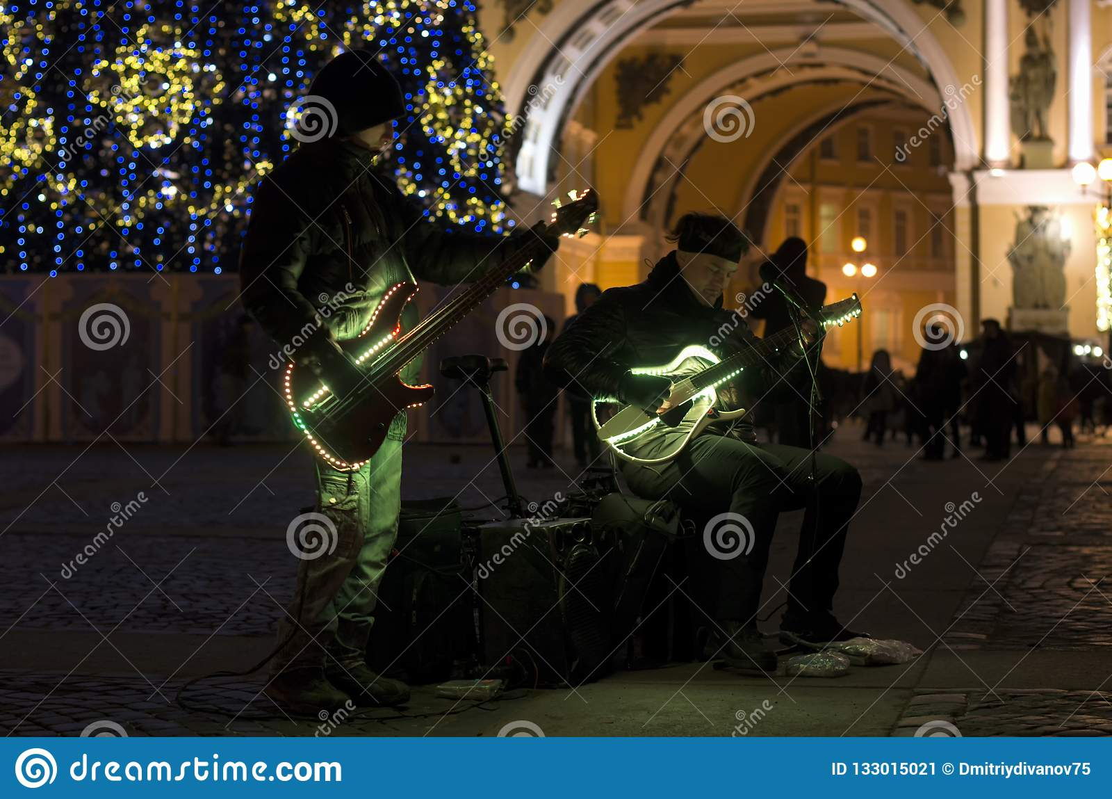 Street musicians with night illumination and Christmas tree
