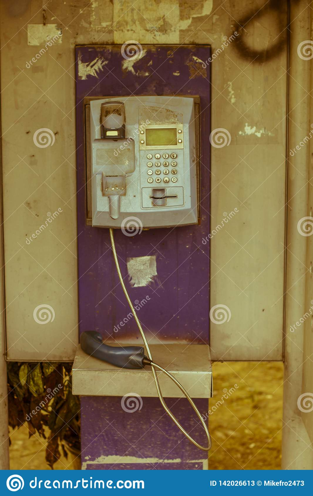 Old payphone out of service in the city