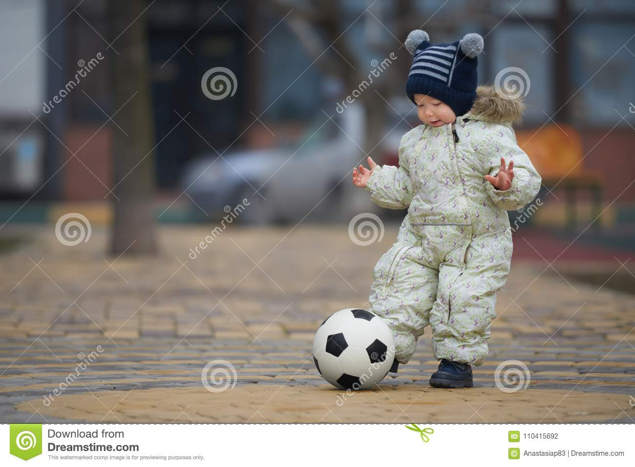 Street portrait of the little boy playing football