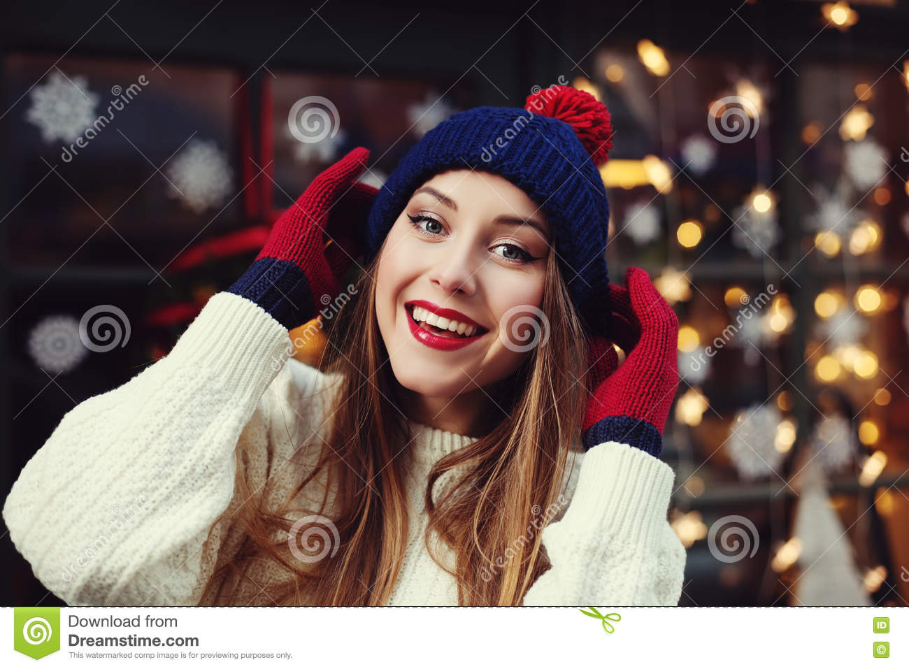 Street portrait of smiling beautiful young woman wearing stylish classic winter knitted clothes. Model looking at camera