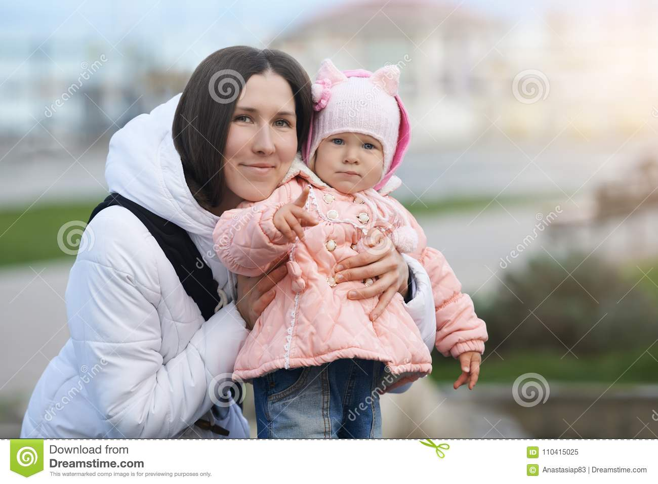 Street portrait of the smiling mother with her serious daughter. Mood difference