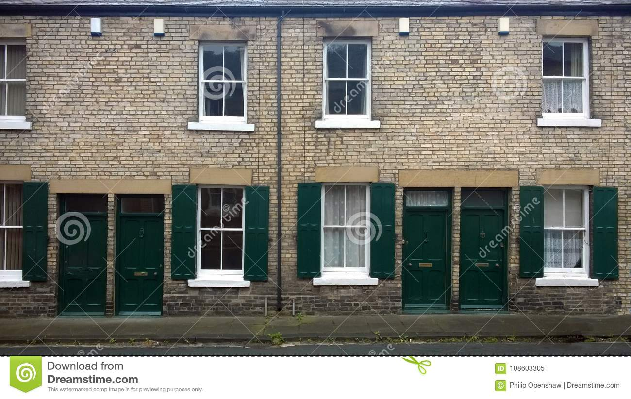 Street with a row of typical british old terraced houses with green doors and window shutters in durham england