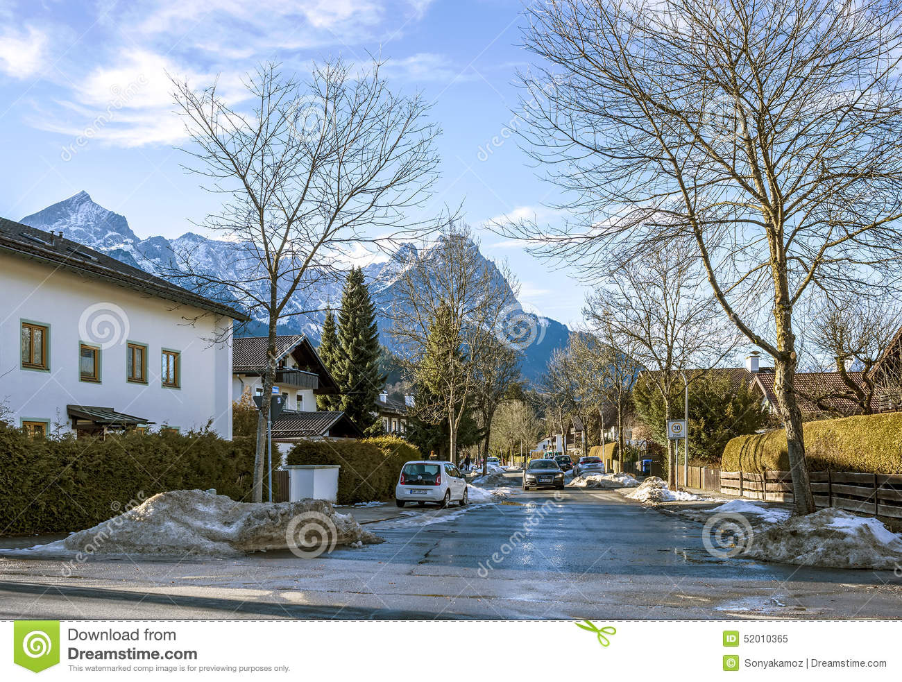 A street of a small alpine town and ski resort with for Designhotel garmisch