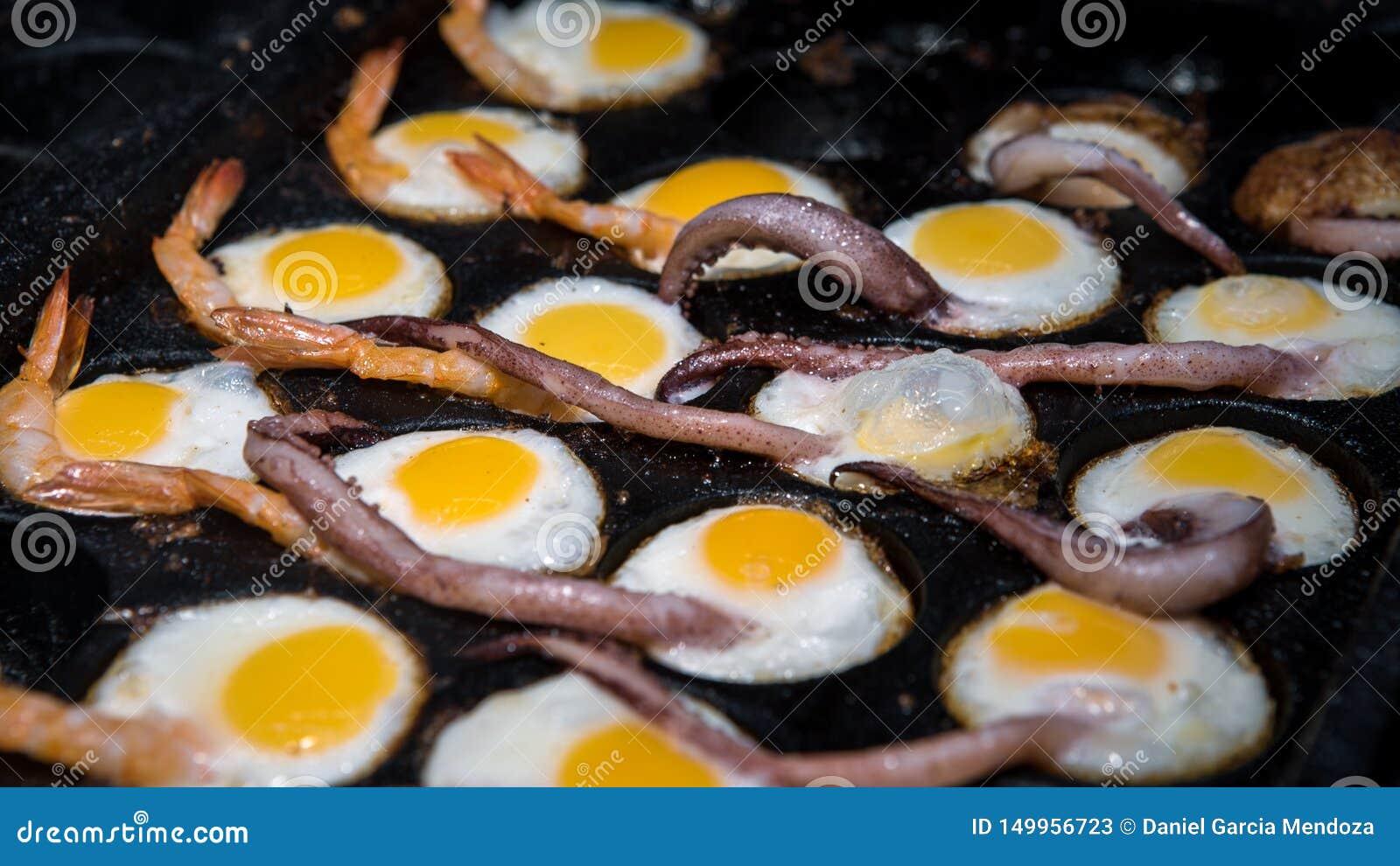 A street vendor prepare fried quail eggs with squid tentacles and prawns
