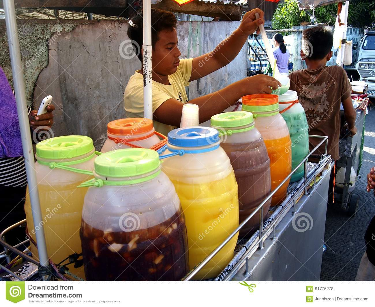 A street vendor sells a variety of fruit juice and other refreshments on his beverage cart at a street in Antipolo City.