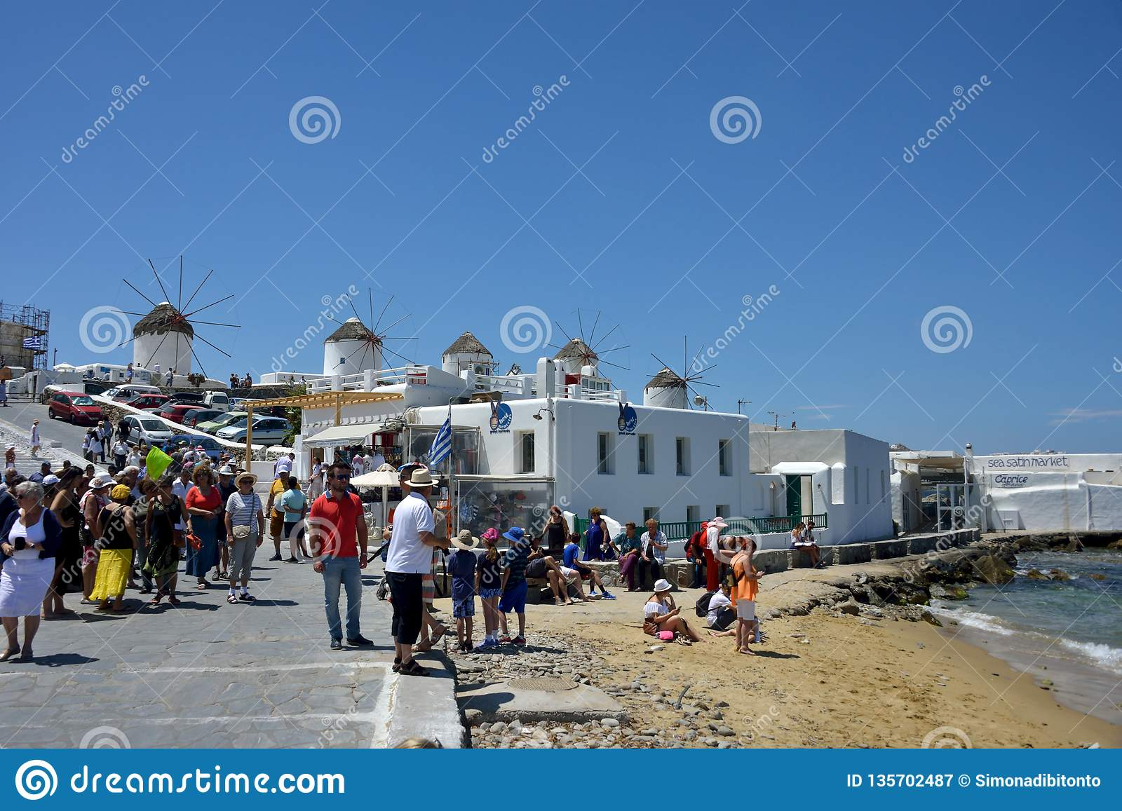 Street view in the Little Venice in Mykonos with tourists walking near the sea and shooting photos