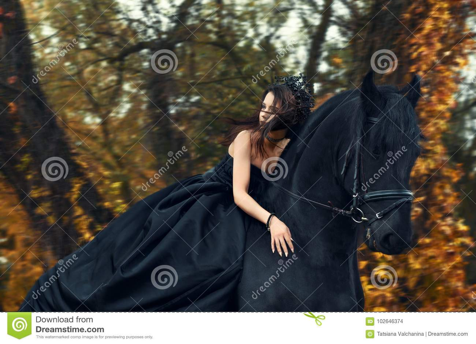 Strega nera della regina della ragazza in vestito nero e diadema che guida a cavallo su un cavallo frisone