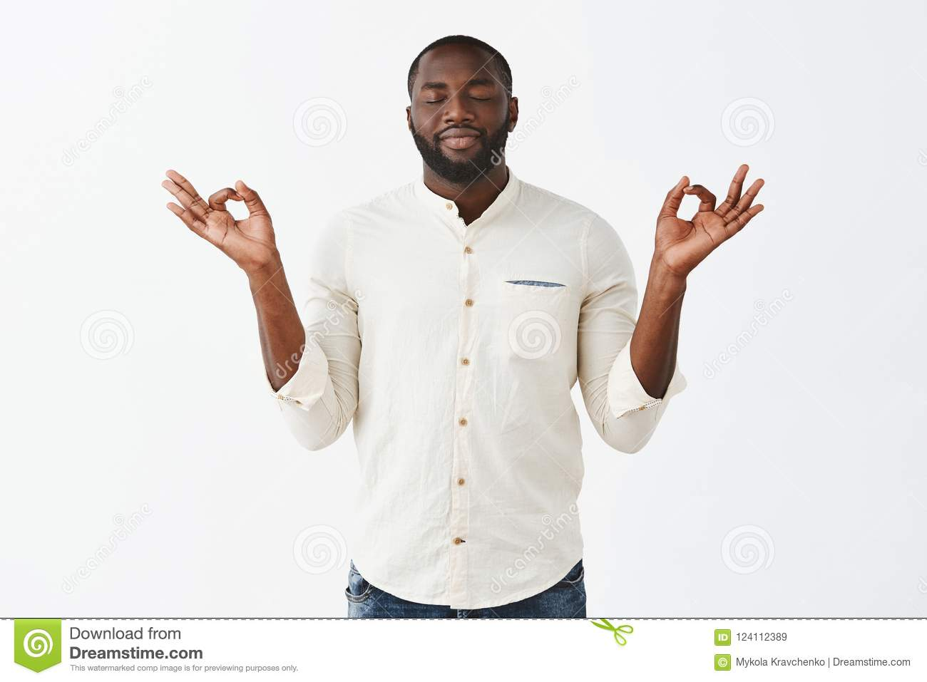 Stress floats away with every minute during meditation. Happy relieved dark-skinned calm man with beard in casual outfit