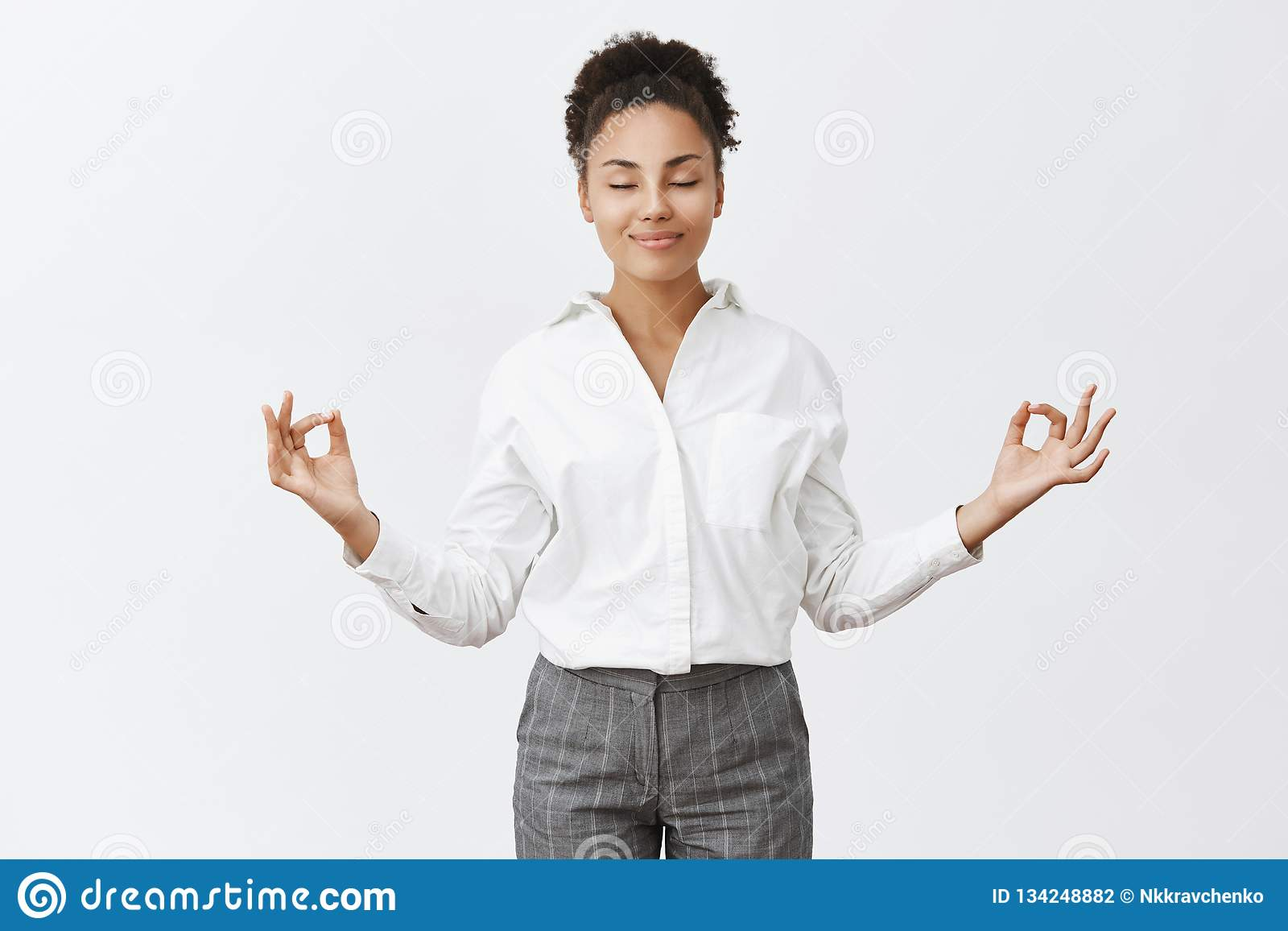 Stress free, only peace inside. Charming relaxed and carefree female in bossy outfit, raising hands in zen gesture