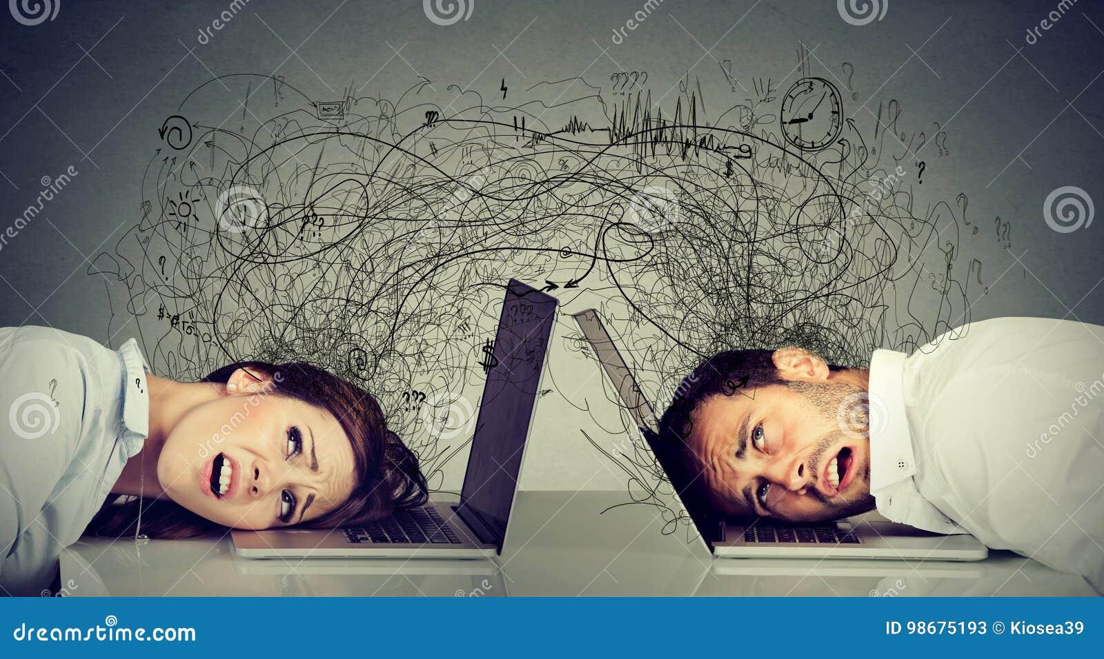 Stressad affärskvinna och man som vilar huvudet på bärbar datorsammanträde på tabellen som frustreras med de som utbyter med röra