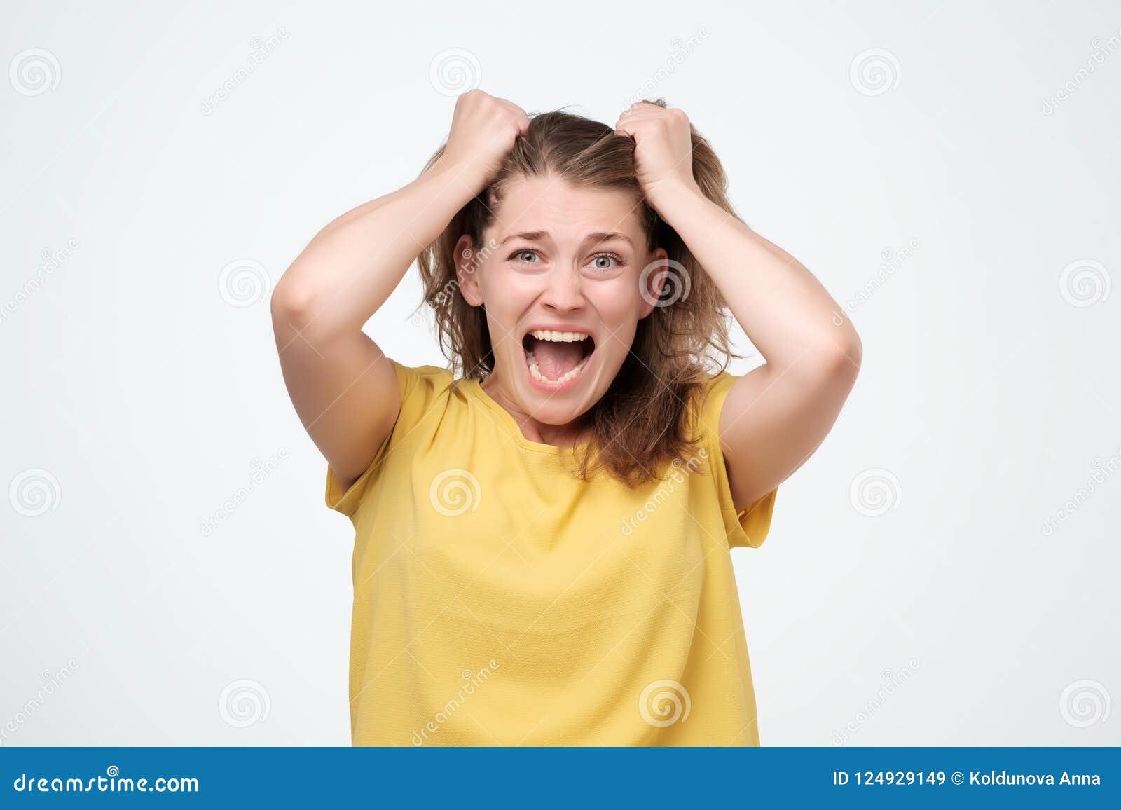 Stressad Closeupstående, frustrerad chockad kvinna som drar hår som skriker ut skrika isolerad grå väggbakgrund