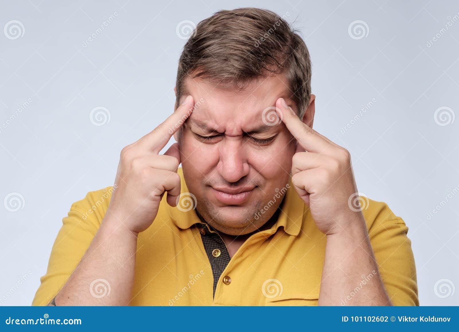 Stressad fet man i gul t-skjorta med fingrar på tempellidande från huvudvärk