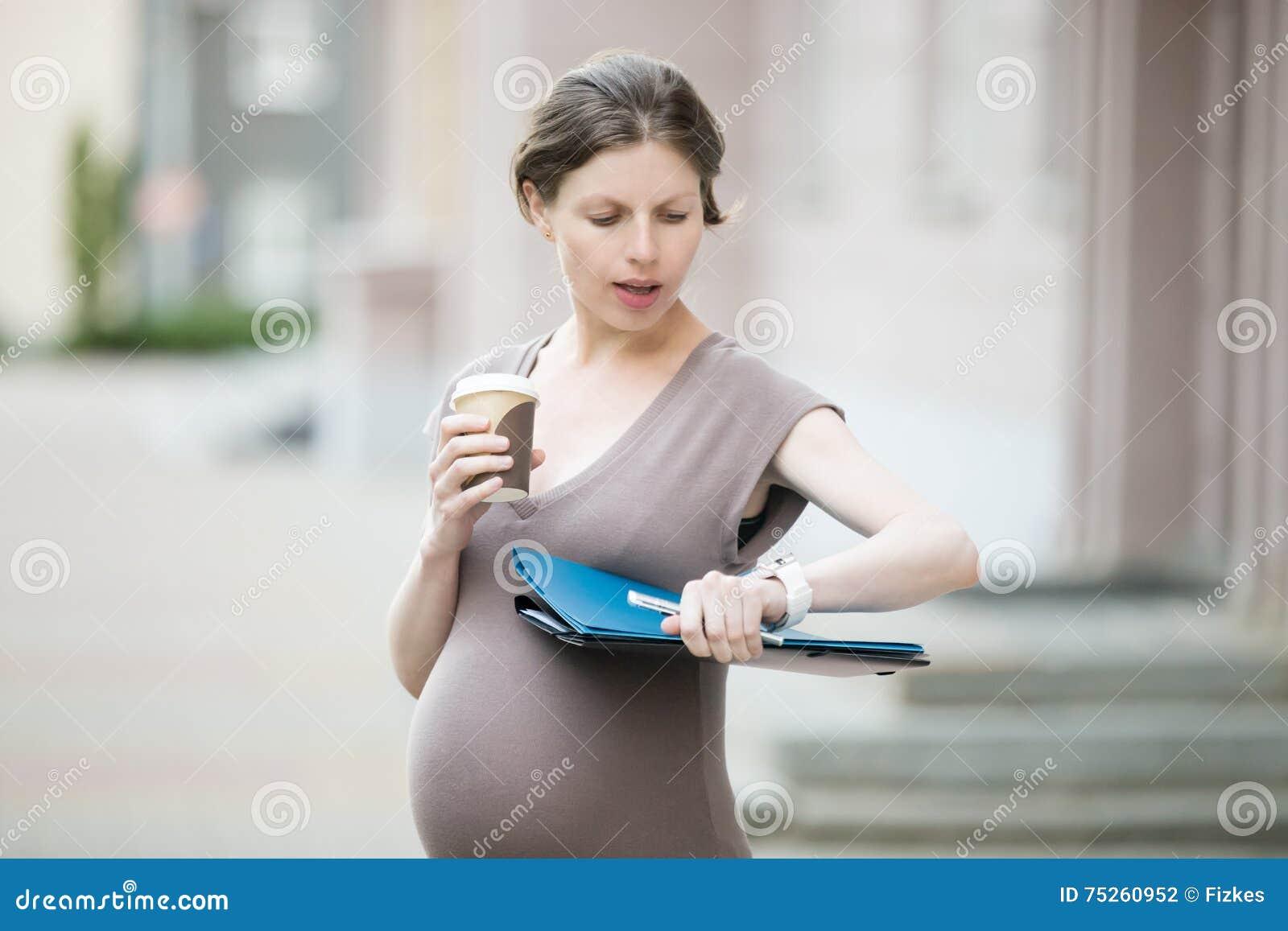 Stressad gravid kvinna som ser klockan