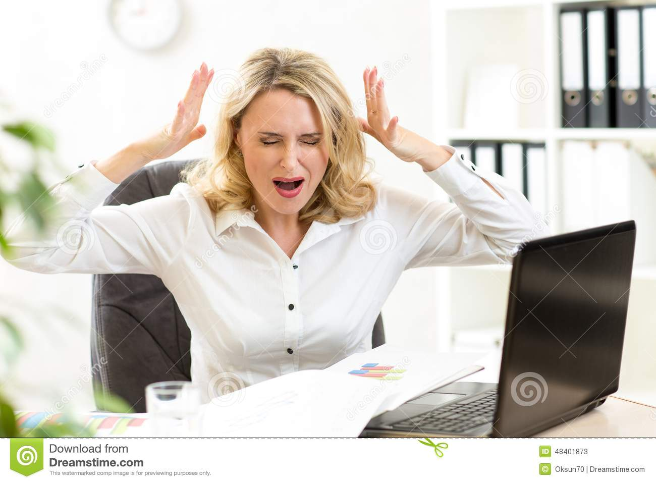 Stressed businesswoman screaming loudly at laptop