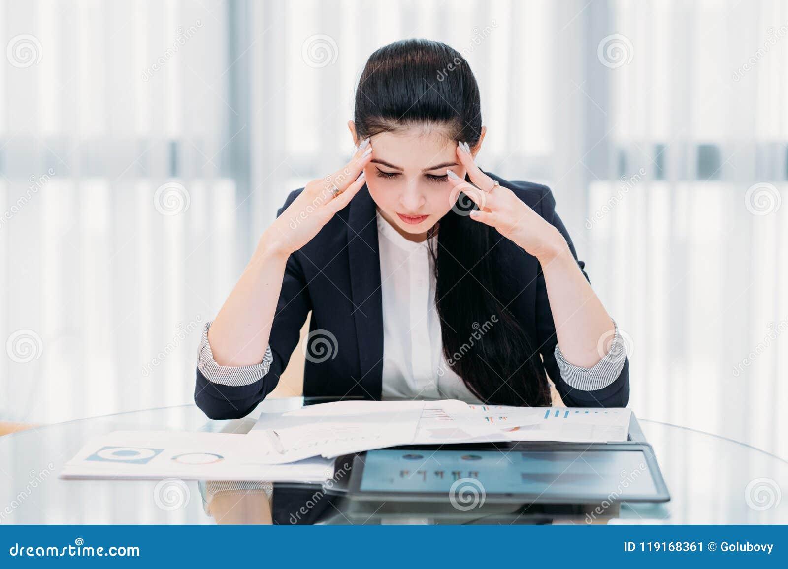Stressed cansó las manos de la cabeza de la mujer de negocios de la oficina