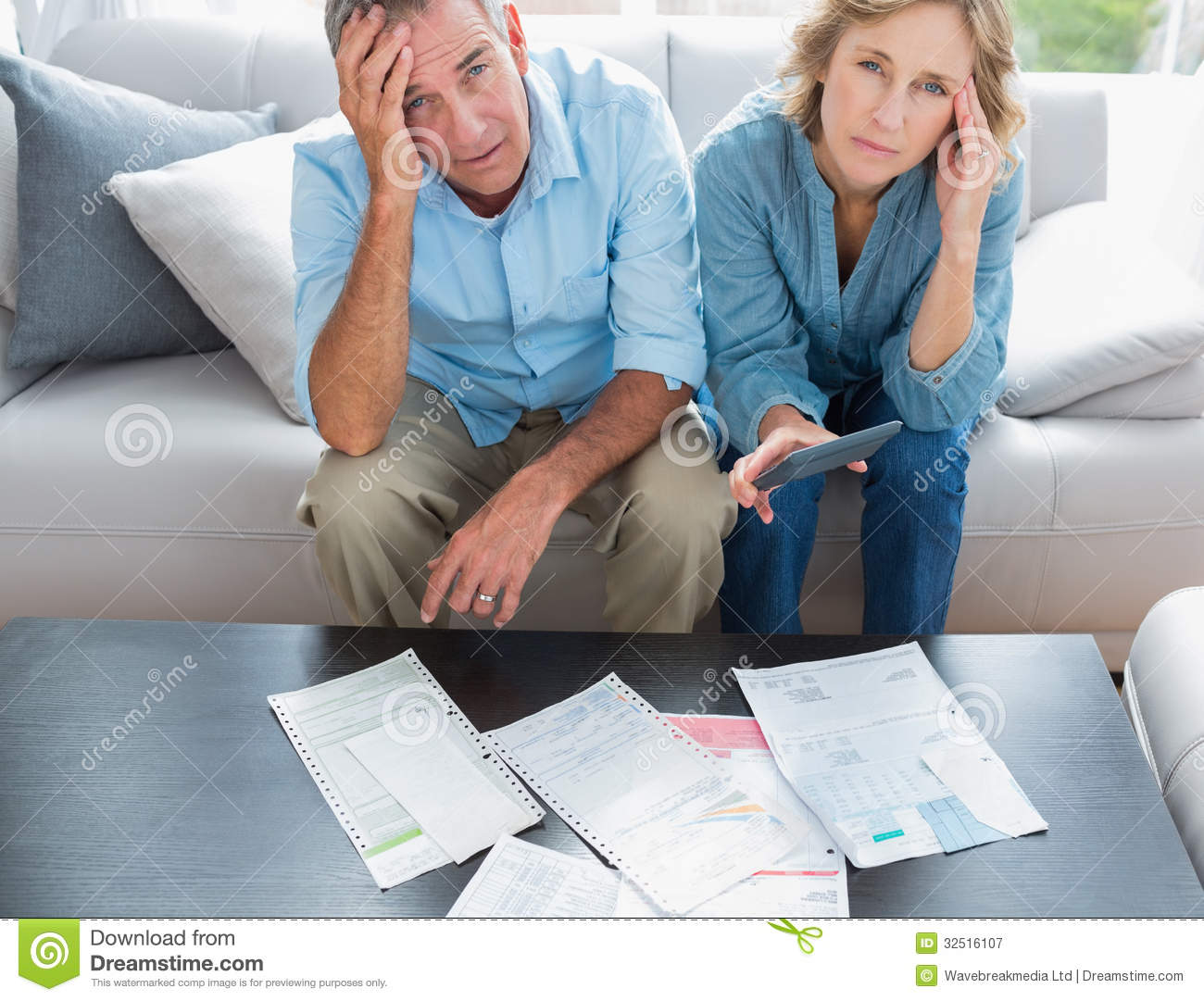 Stressed Couple Sitting On Their Couch Paying Their Bills