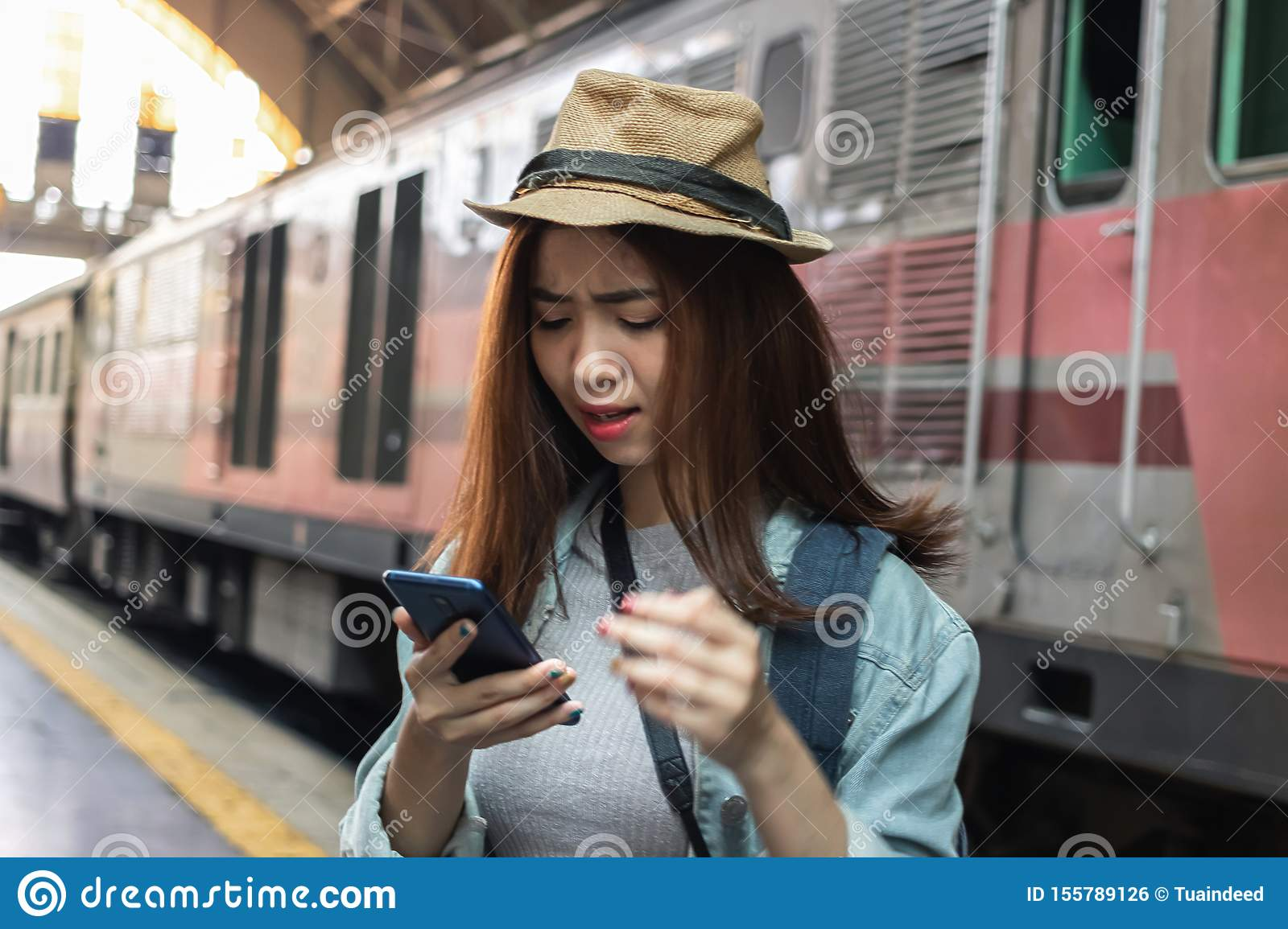 Stressed depressed young Asian backpacker looking phone and feeling shock and frustrated after miss a train. Problem and travel