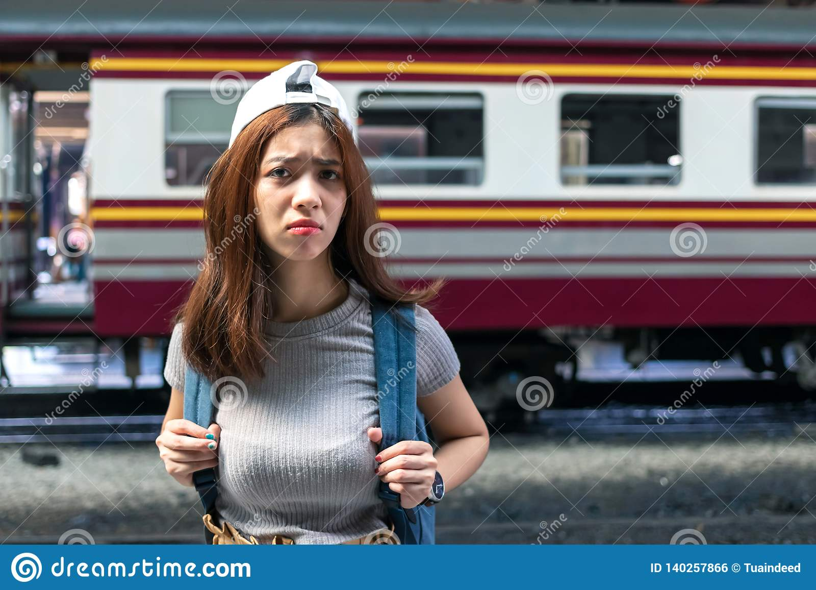 Stressed depressed young Asian lady tourist feeling shock and frustrated after miss a train. Problem and travel lifestyle concept