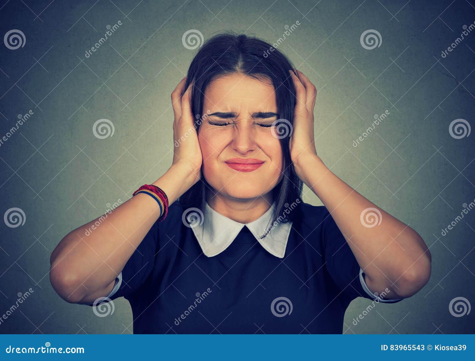 Stressed ha frustrato la donna che copre le sue orecchie di mani