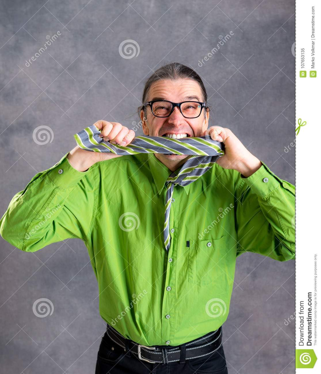 Stressed man in green shirt and glasses biting in his necktie