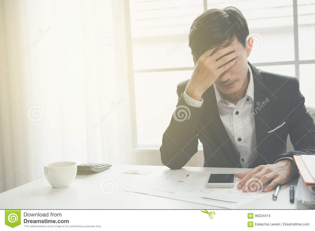 A stressed out business man holds his head in despair