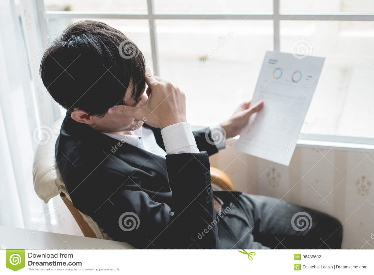 A stressed out business man holds his head