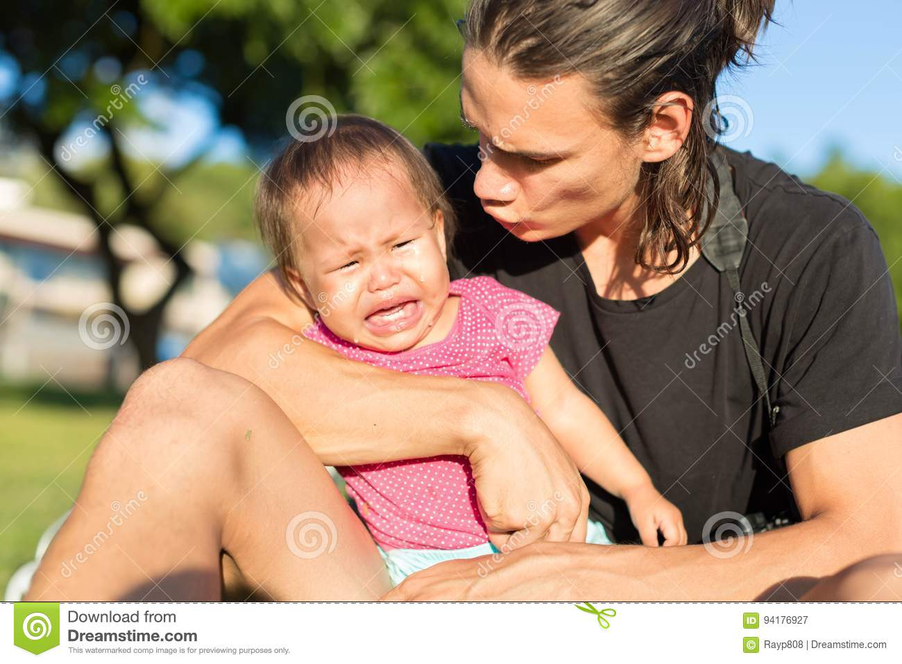 Stressed out and frustrated father tries to comfort his upset toddler daughter from crying in a park setting.