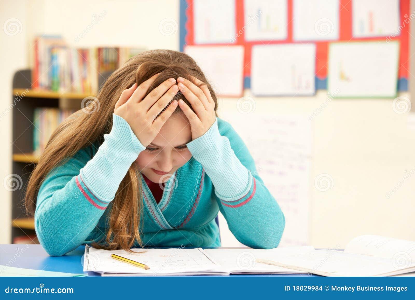 Stressed Schoolgirl Studying In Classroom