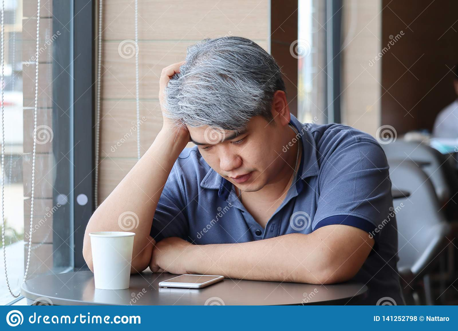 Stressed tired young Asian middle-aged man,old man take hand on head feeling depression and exhausted sitting by the window at