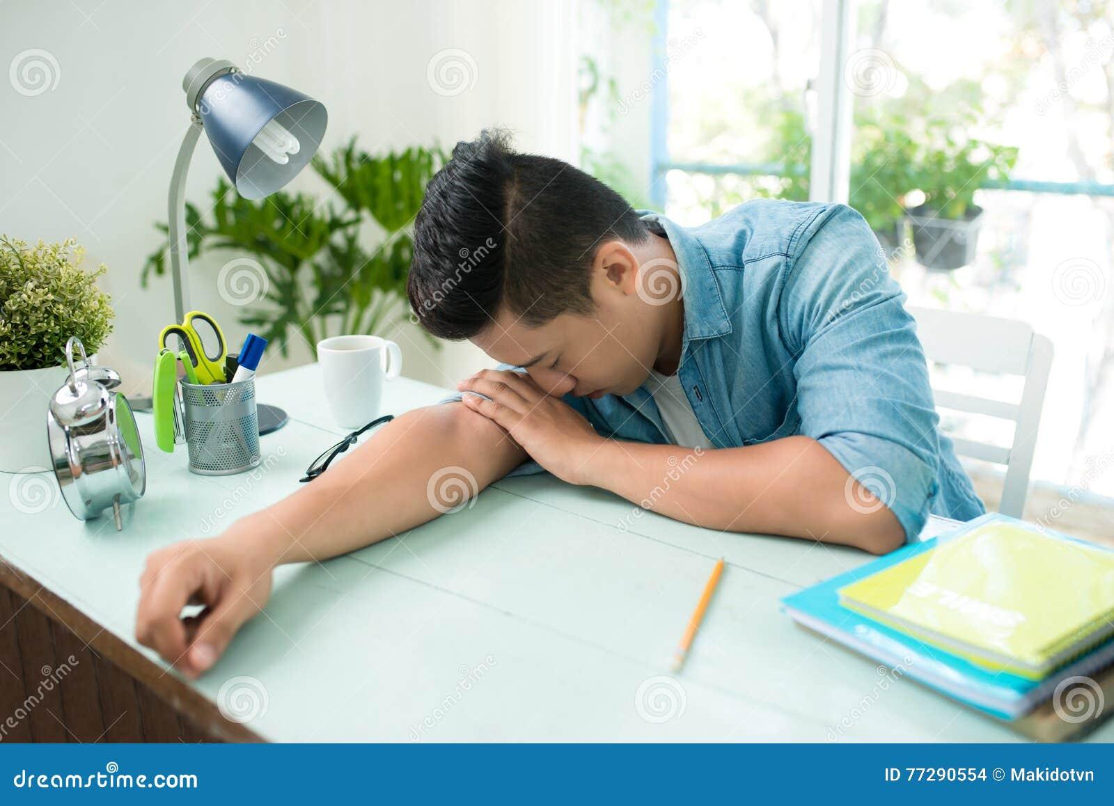 Stressed trabajó demasiado estudiar del hombre soñoliento en el escritorio