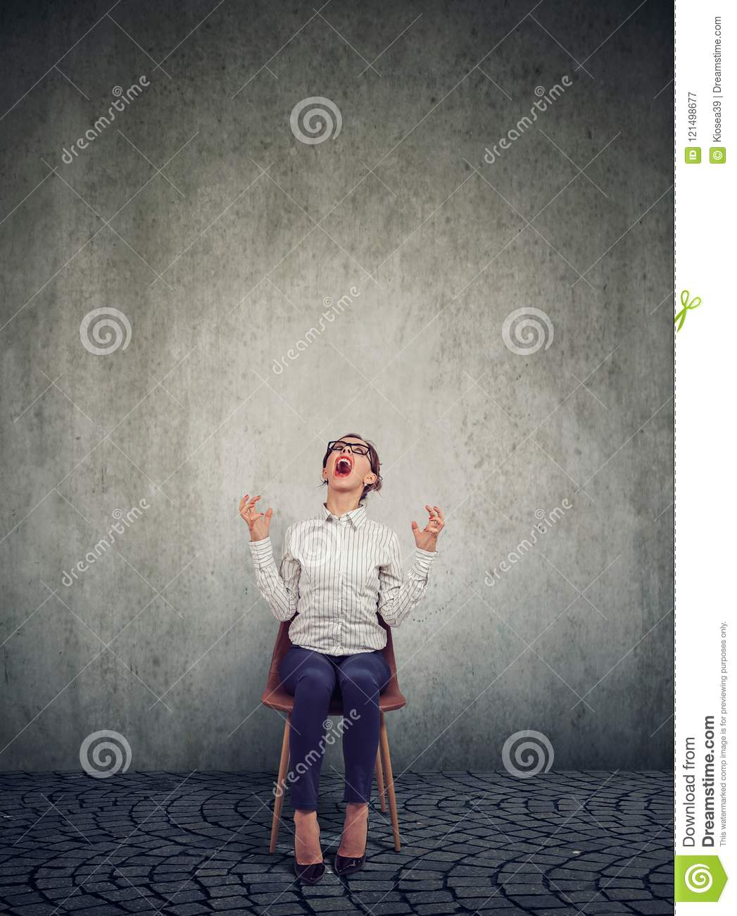 Stressed woman company employee sitting on a chair screaming in desperation