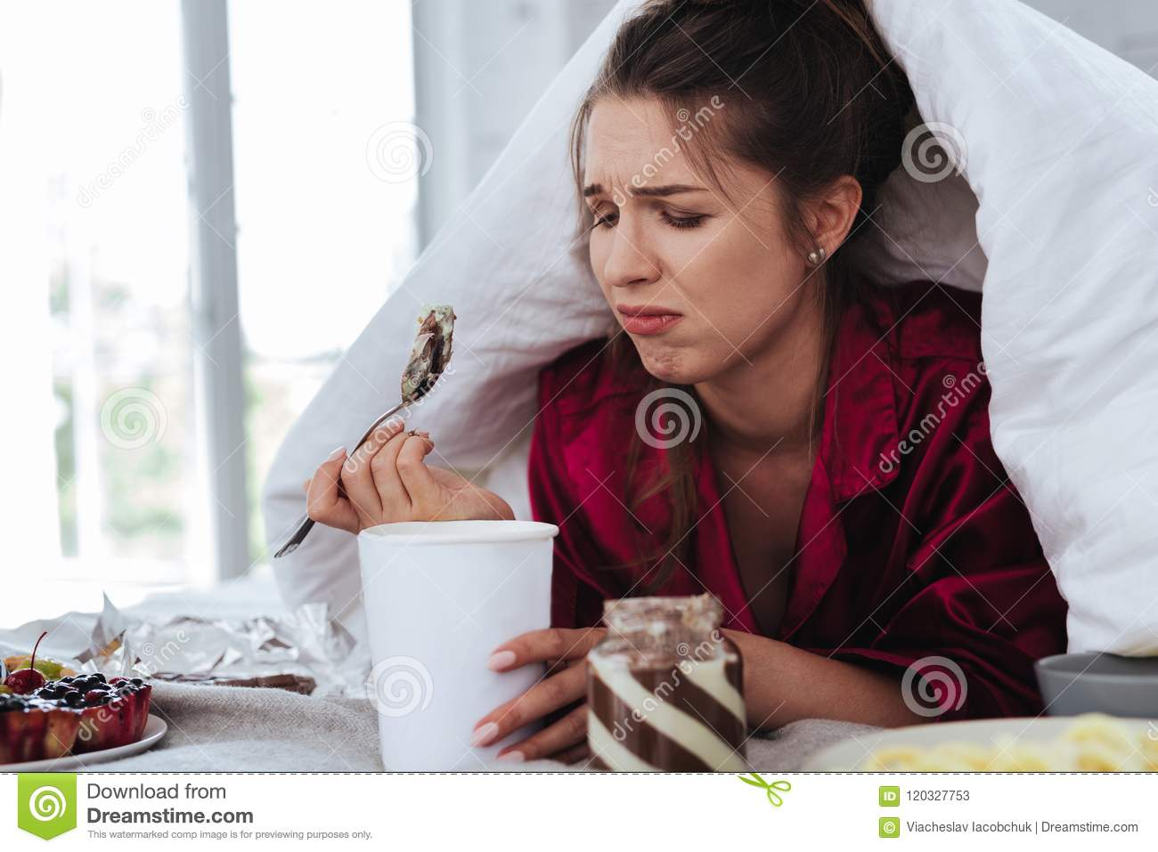 Stressed woman hiding under coverlet eating ice cream