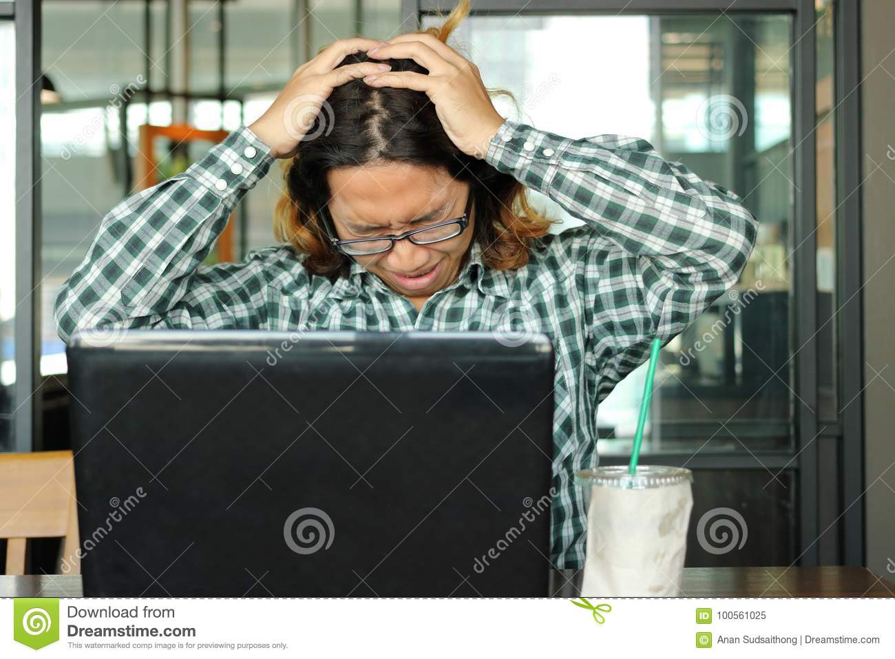 Stressed young Asian business man with hands on head feeling tired against his work in office. Exhausted and overwork job concept.