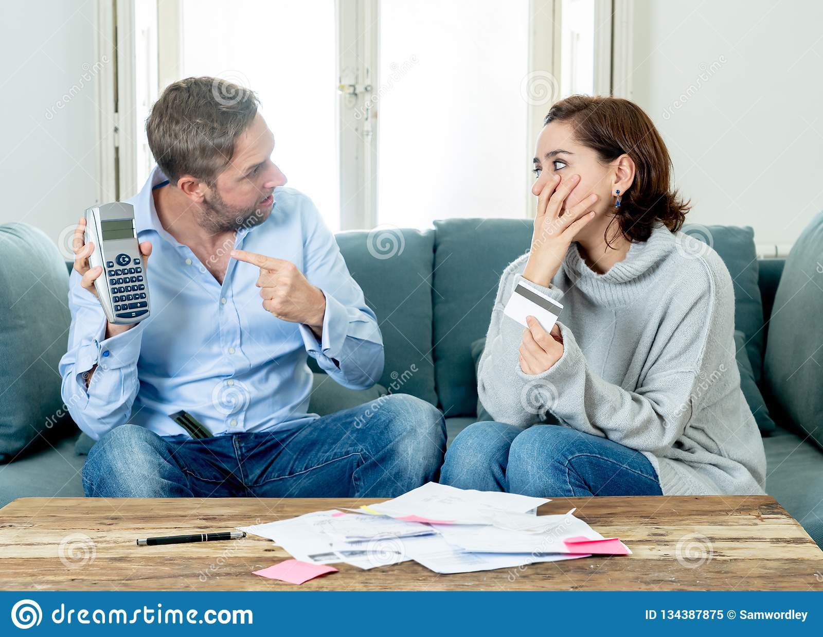 Stressed young couple having an argument over credit car debts payments and home finance