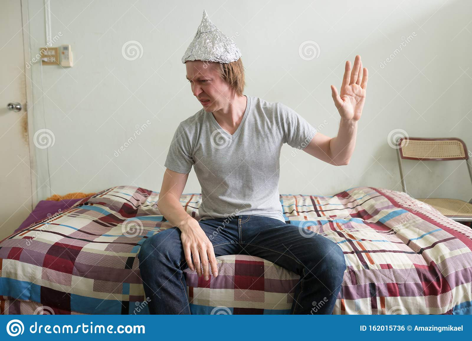 Stressed Young Man With Tin Foil Hat Showing Stop Gesture In The Bedroom Stock Photo Image Of Adult Horror 162015736