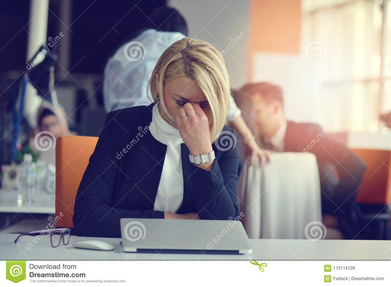 Feeling tired and stressed. Frustrated adult woman keeping eyes closed from fatigue while sitting in office.
