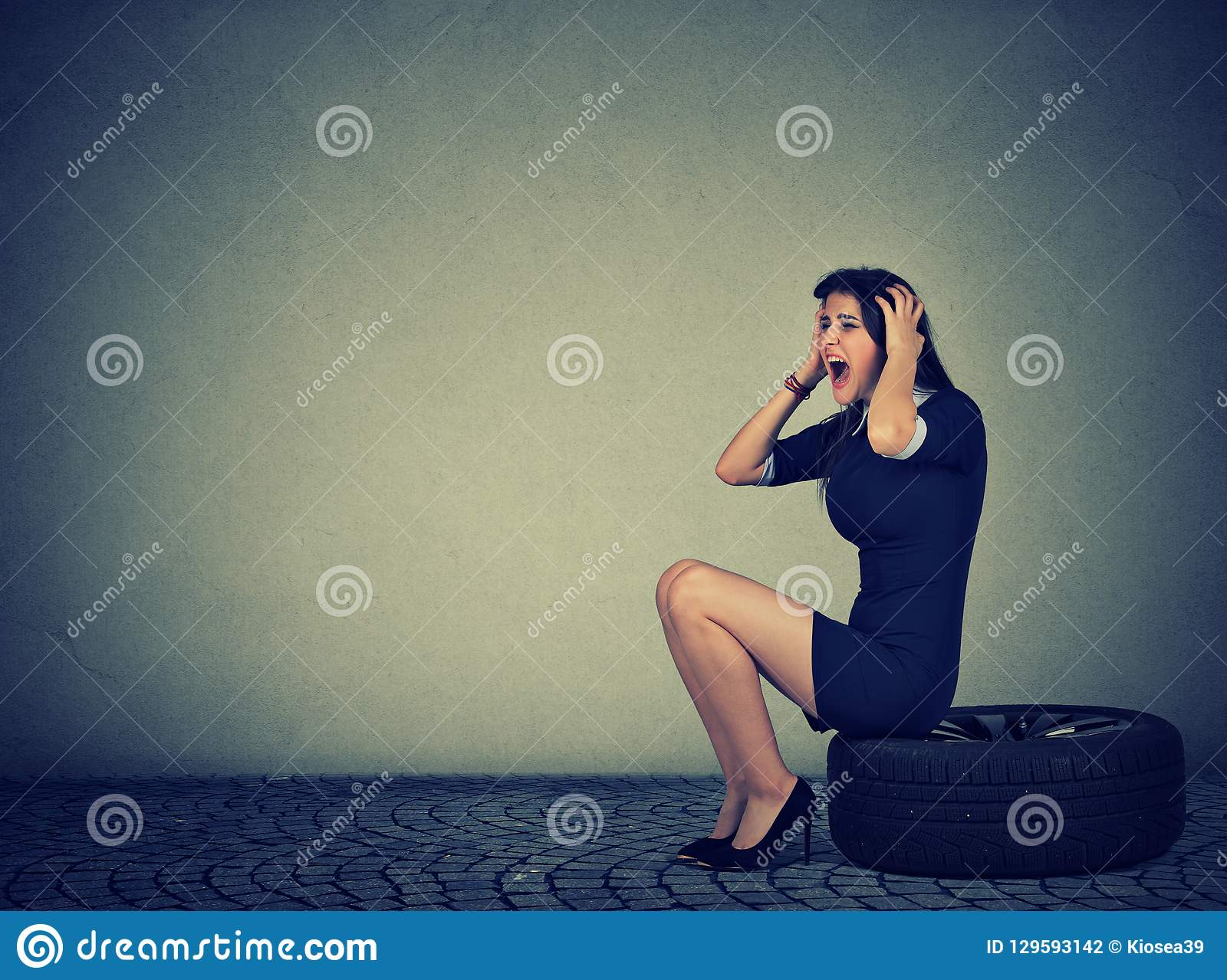 Stressful woman screaming while sitting on tire