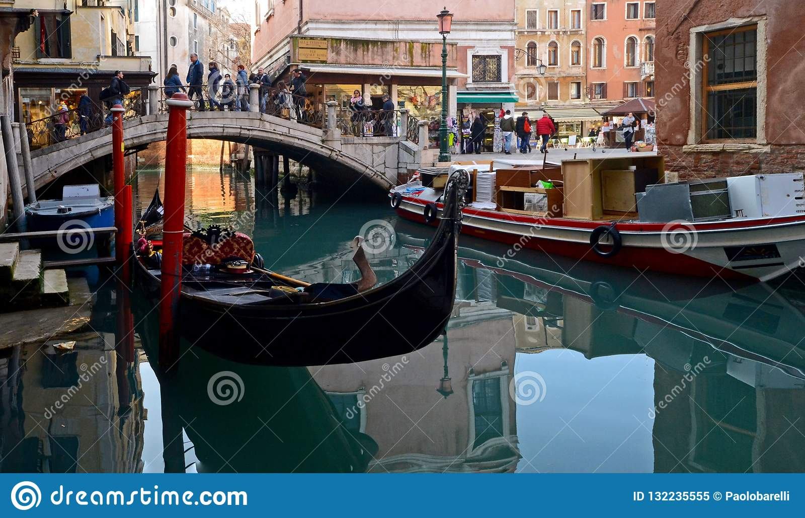 A stretch of a canal in Venice with boats and colorful buildings on a sunny winter day