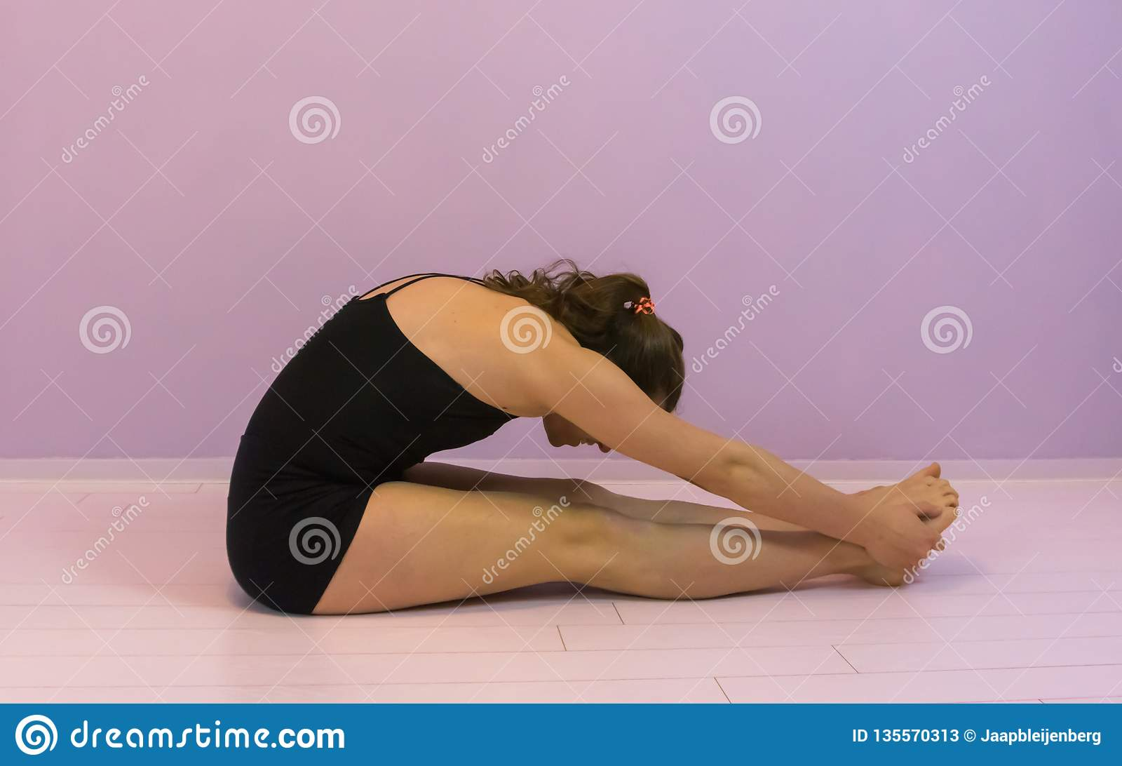 Stretching the calves to train flexibility, sport work out, LGBT young transgender girl working out