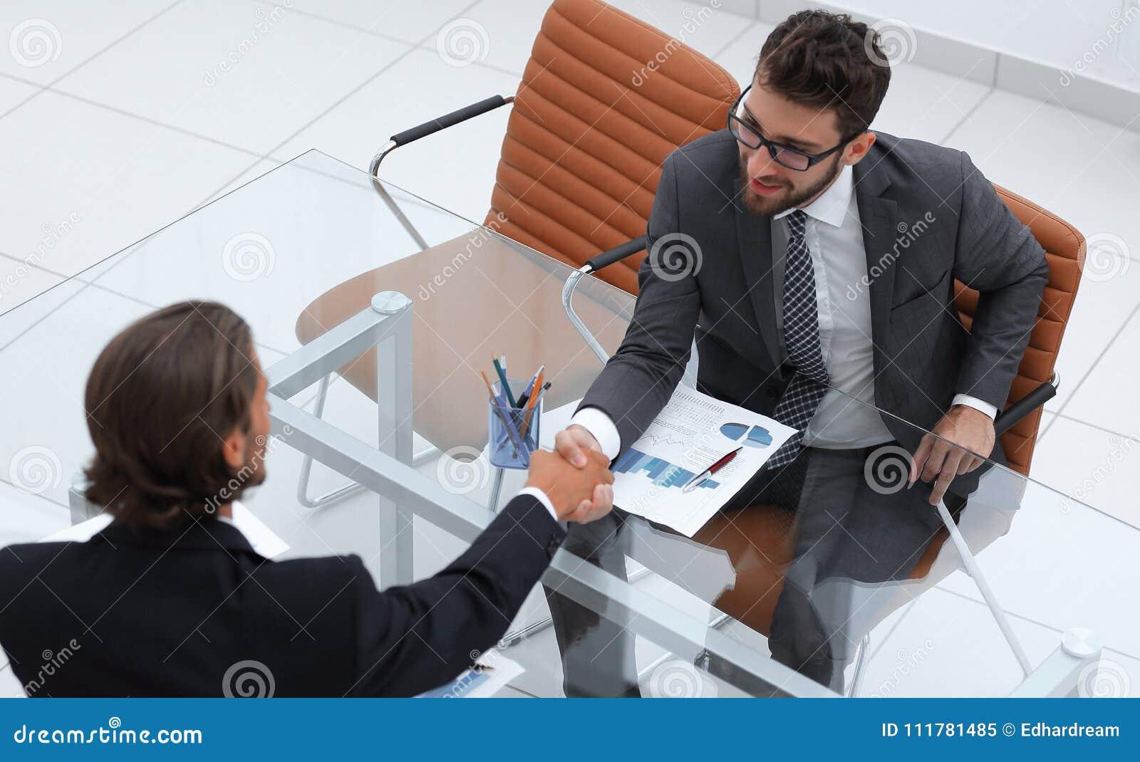 Stretta di mano dei soci commerciali che si siedono al loro scrittorio