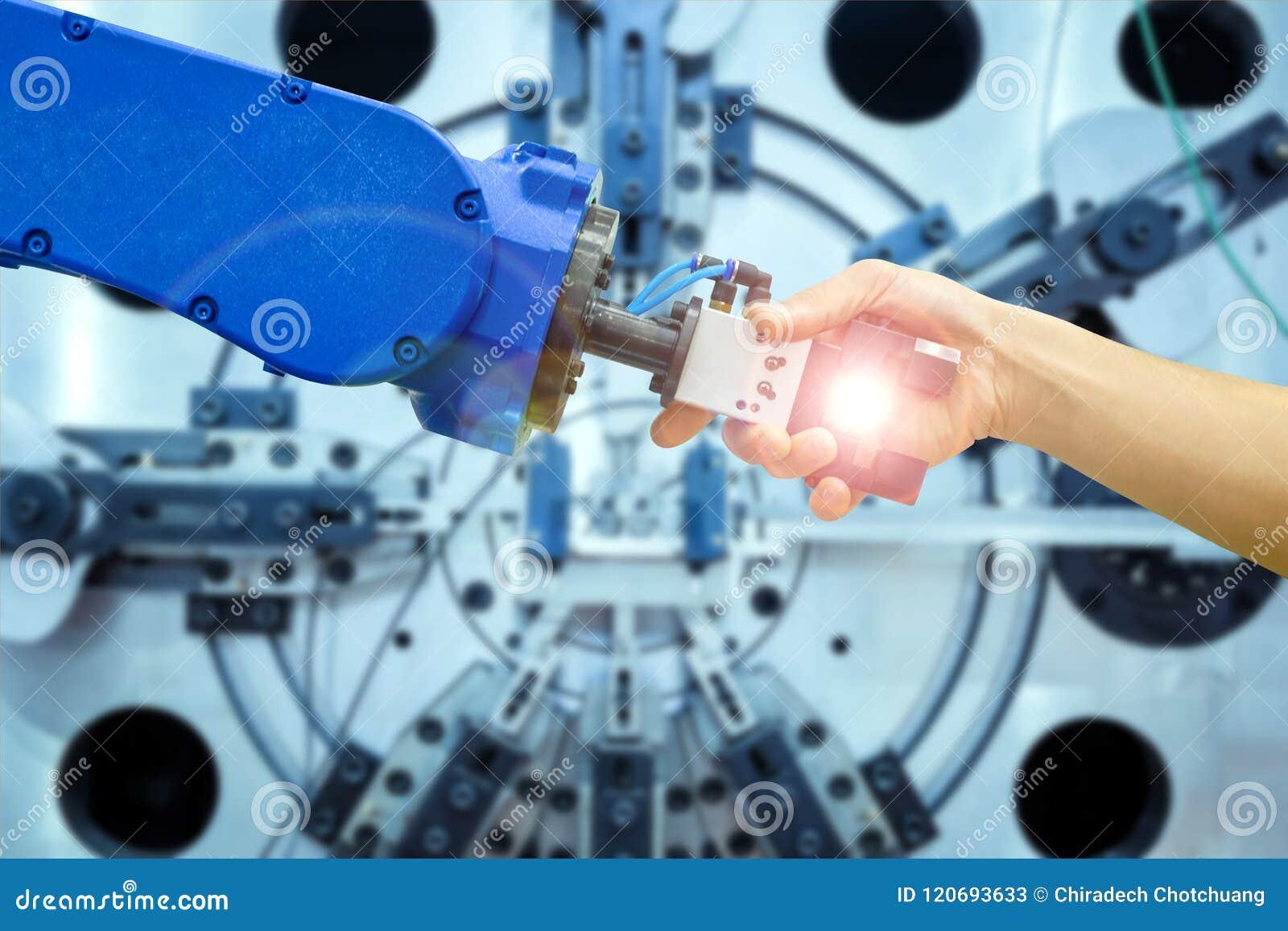 Stretta di mano del robot industriale con l essere umano sulla relazione per lavorare alla fabbricazione industriale