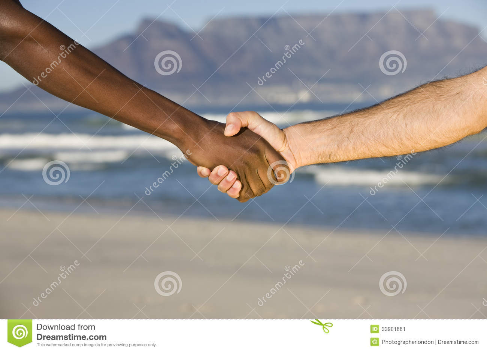Stretta di mano multietnica alla spiaggia della montagna - Alla colorazione della spiaggia ...