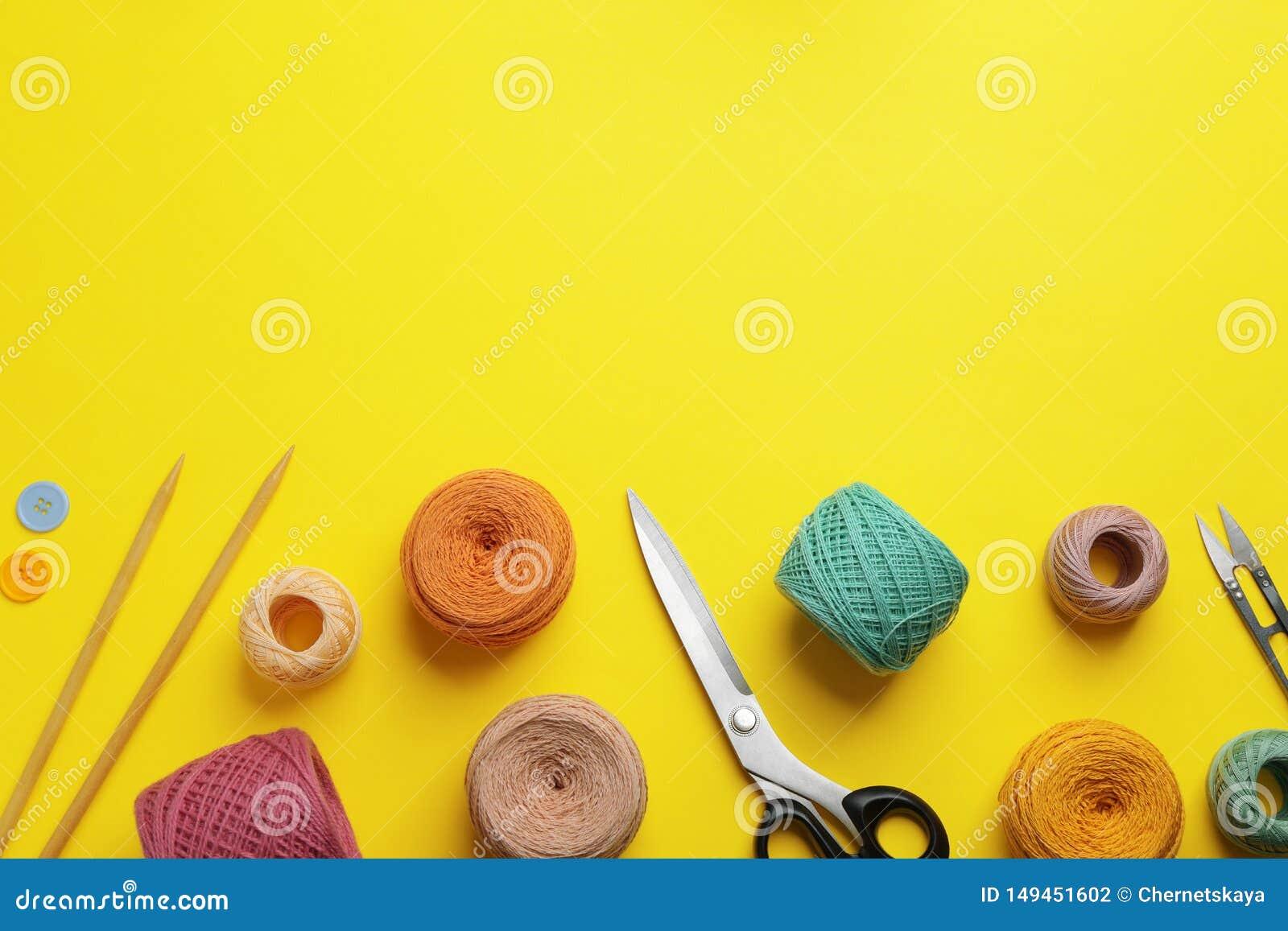 Strickende Faden und nähendes Material auf Farbhintergrund, flache Lage
