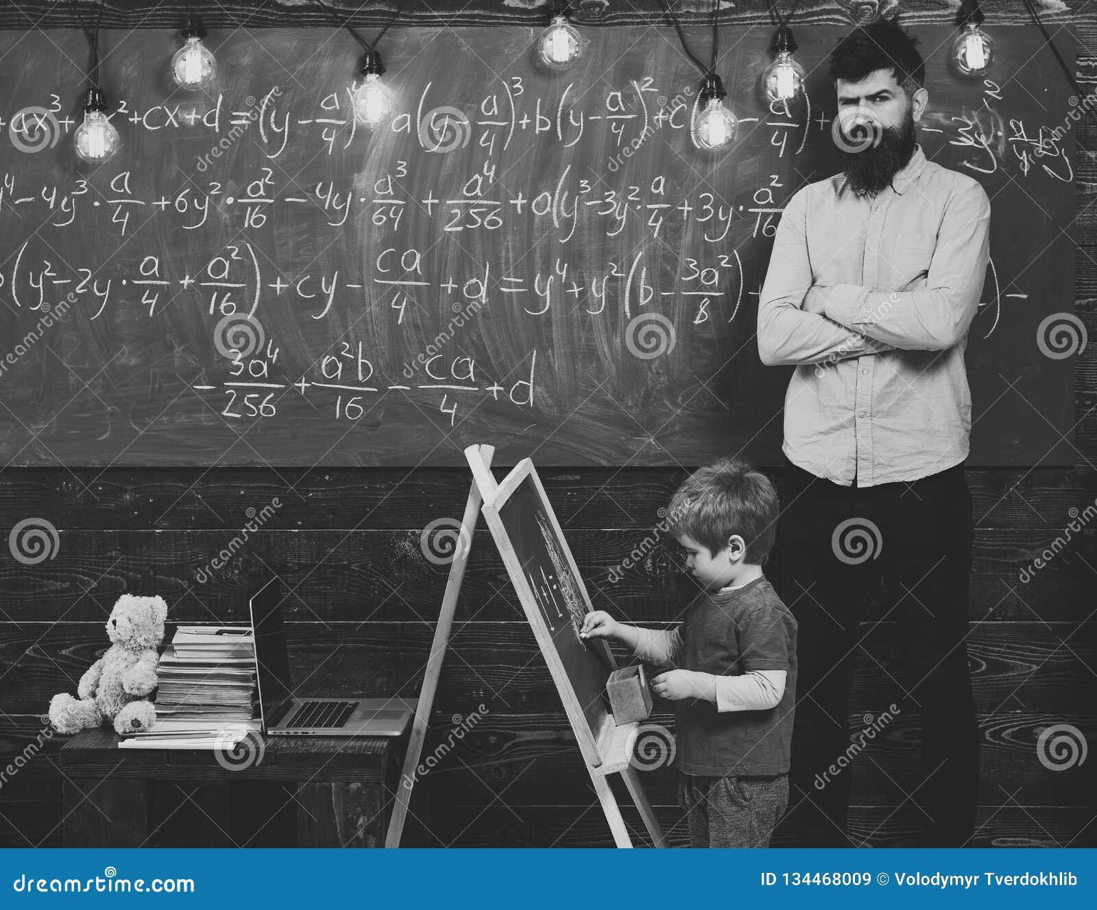 Strict math teacher checking pupil s work. Blond schoolboy solving equation at chalkboard. Preschool education concept