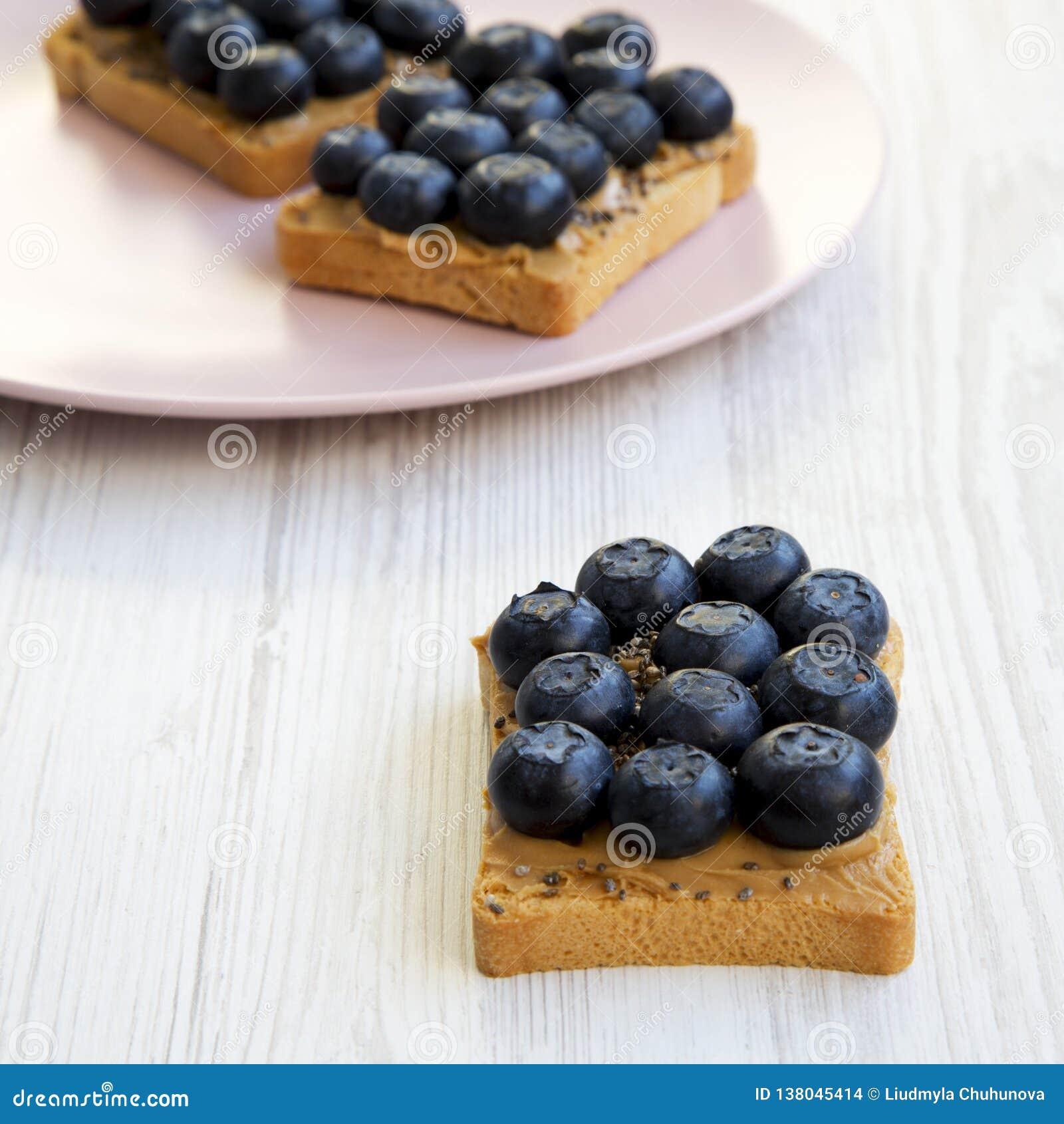 Strikt vegetarianrostade bröd med jordnötsmör, blåbär och chiafrö på en vit trätabell, sidosikt selektiv fokus för sund frukost