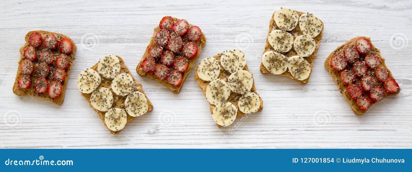 Strikt vegetarianrostade bröd med jordnötsmör, frukter och chiafrö på en vit trätabell, över huvudet sikt Sund frukost som bantar
