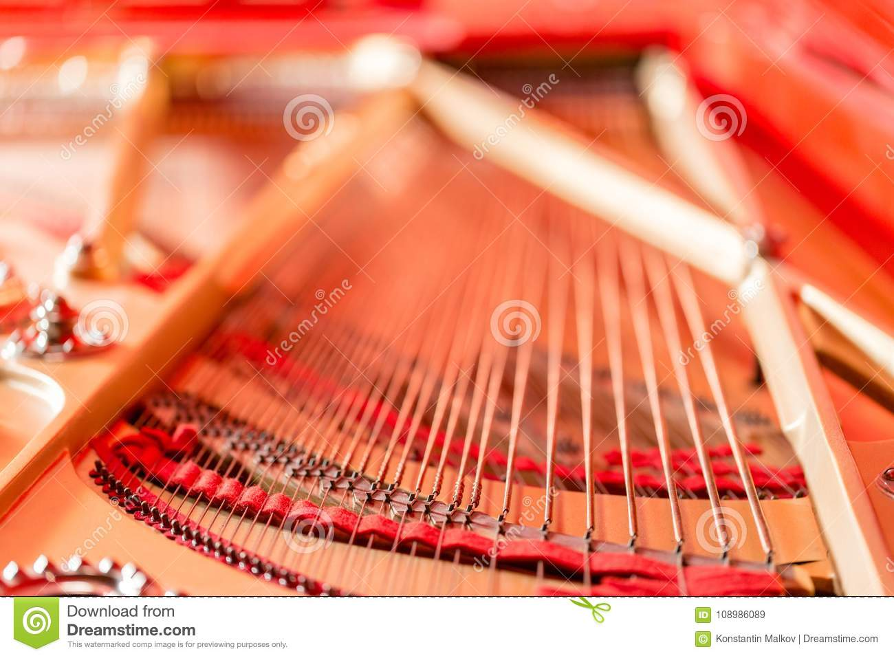 Strings close-up. Vintage red classical grand piano. Musical instrument abstract.