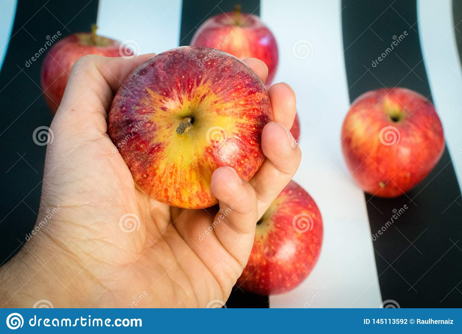 Striped черно-белая предпосылка Удерживание руки и яблоко и красные яблоки на striped черно-белой предпосылке, как a