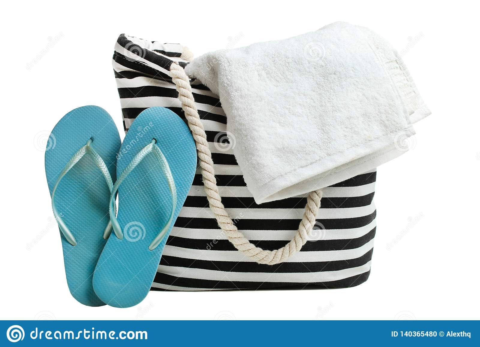 41dde6218 One striped beach bag with white bath towel and blue rubber slaps isolated  on white. Concept summer, vacation on the beach